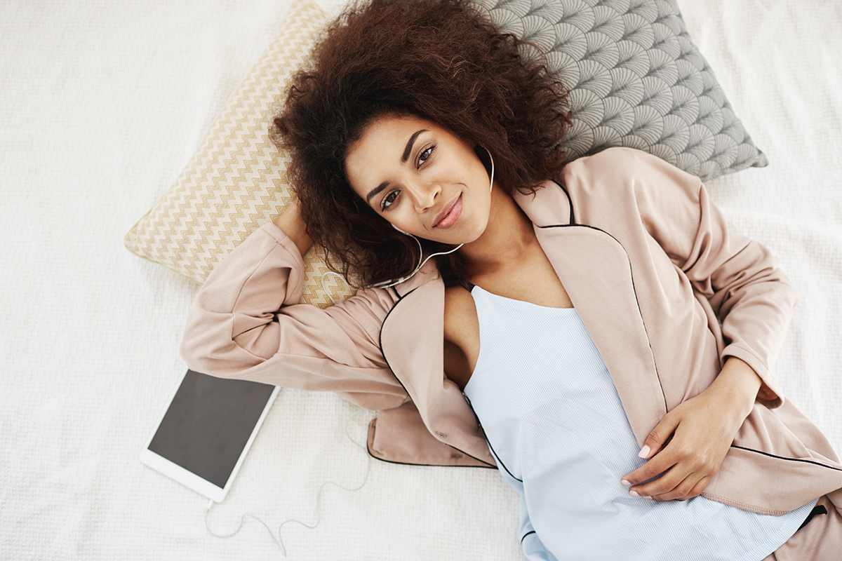 Ato de vestir - Jovem moça preta deitada na cama com roupa fashion